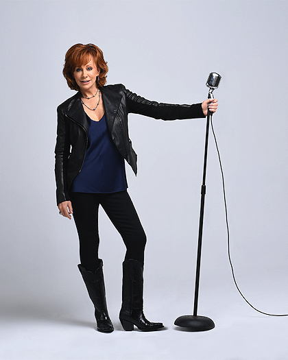 Reba McEntire standing and holding a classic microphone