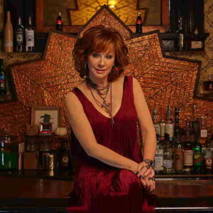 Reba McEntire wearing a sleeveless red dress