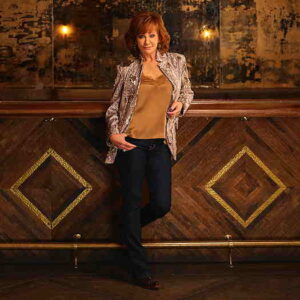Reba McEntire leaning against a bar