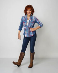 Reba McEntire wearing a blue flannel shirt, blue jeans and cowboy boots
