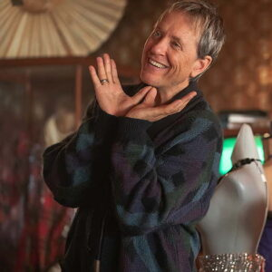 Richard E. Grant holding his hands up to his face and smiling