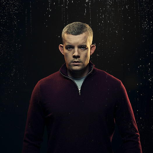 Russell Tovey wearing a red jacket.