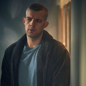 Russell Tovey wearing a robe with a blue shirt underneath