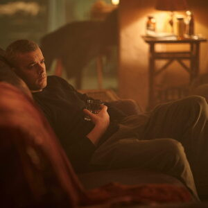 Russell Tovey sitting on a couch with a drink