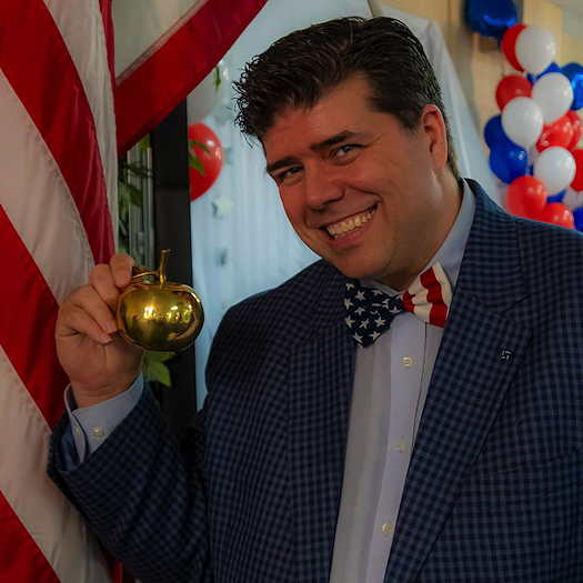 Shane Vaughn wearing a suit with a USA flag bow tie and holding a golden apple