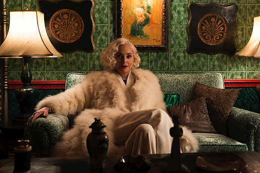 Sharon Stone sitting on a sofa wearing a white fur coat