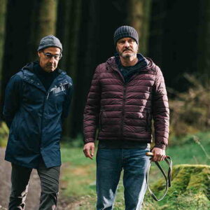 Stanley Tucci walking on a path in the woods