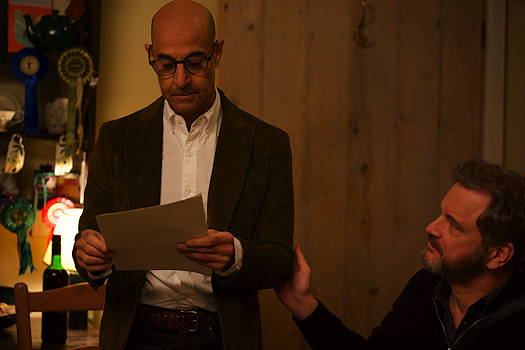 Stanley Tucci standing and reading a piece of paper