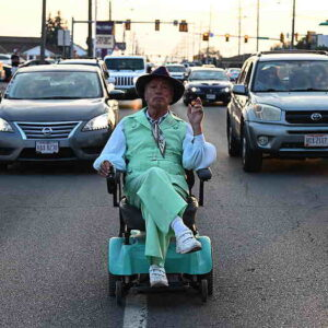 Older gentleman riding a Hoveround down the middle of a busy street