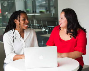 Two women talking to each other in front of a laptop