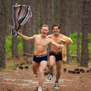 Two young men running shirtless through the woods