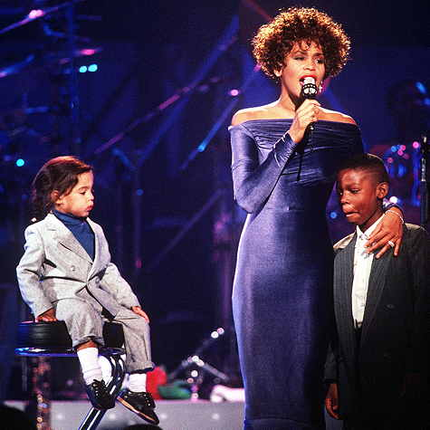 Whitney Houston on stage with two children