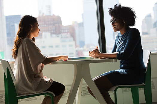 Two women sitting at a table talking to each other
